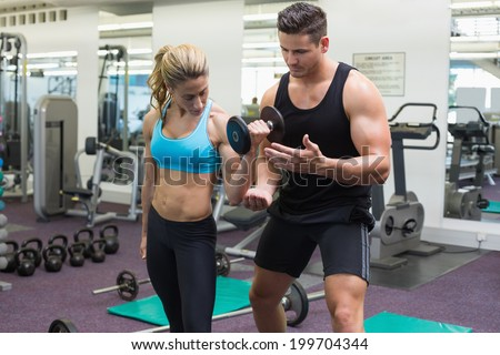 Personal trainer coaching female bodybuilder lifting dumbbell at the gym