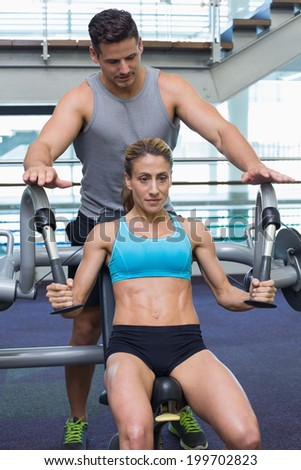Personal trainer coaching female bodybuilder using weight machine at the gym