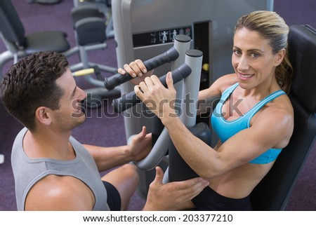 Personal trainer coaching smiling female bodybuilder using weight machine at the gym - stock photo