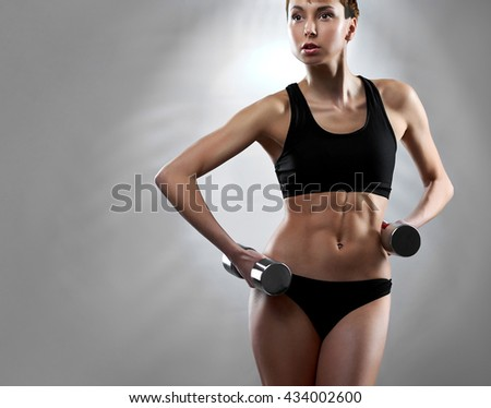 Personal trainer. Cropped portrait of a healthy and fit young woman exercising with weights at the studio looking away