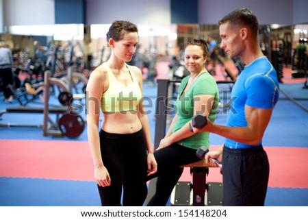 Personal trainer demonstrating a bicep exercise. At the gym. Selective focus. - stock photo