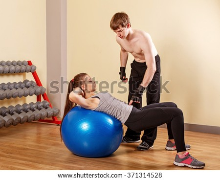 Personal trainer helping a girl learn to press fitbar. Fitness club. Weight loss program. Health and Fitness. - stock photo