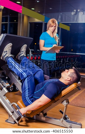 Personal trainer helping a men working out on leg press machine in gym