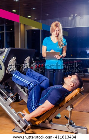 Personal trainer helping a men working out on leg press machine in gym - stock photo