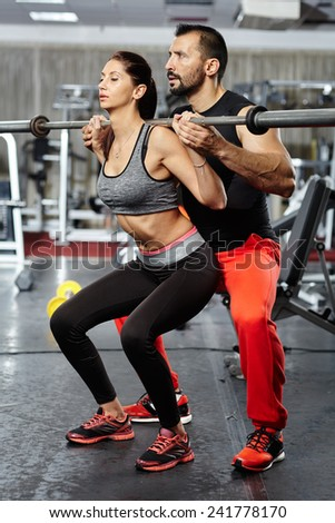 Personal trainer helping a young woman doing squat exercises with barbell in a gym - stock photo