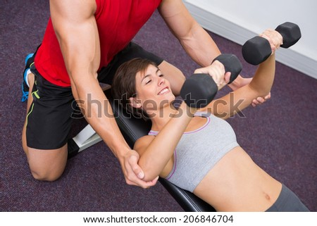 Personal trainer helping client lift dumbbells at the gym - stock photo