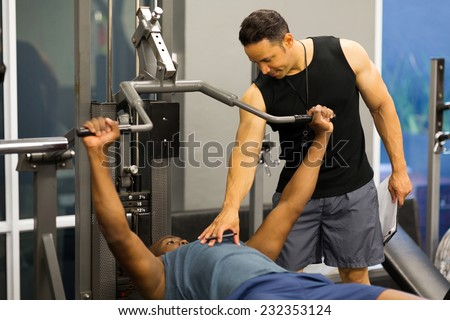 personal trainer helping client lift weights at the gym - stock photo