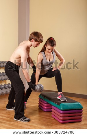 Personal trainer helping girl learn exercise with dumbbells. Fitness club. Weight loss program. Health and Fitness. - stock photo