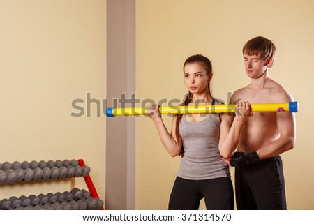 Personal trainer helping girl learn exercise with fitbar. Fitness club. Weight loss program. Health and Fitness. - stock photo
