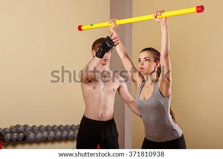 Personal trainer helping girl learn exercise with fitbar. Fitness club. Weight loss program. Sport and health. - stock photo