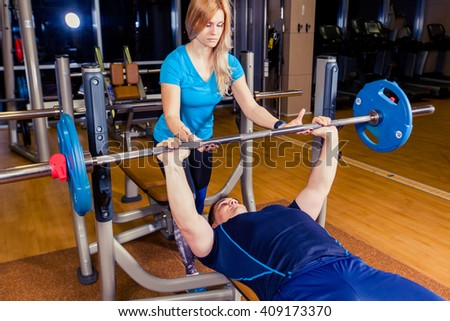 Personal trainer helping  men lift a barbell while working out in  gym - stock photo