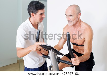 Personal trainer helping with spinning exercise