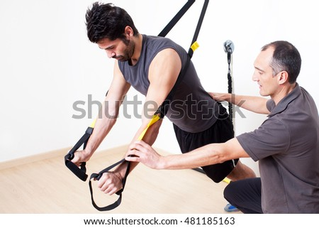 Personal trainer helping with suspension stretching exercise