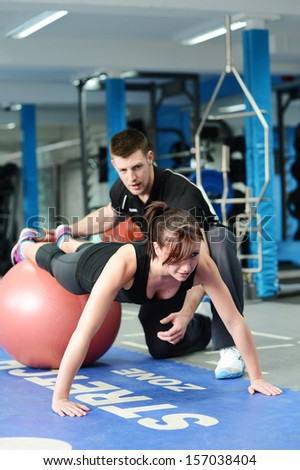 Personal trainer helping young woman in gym - stock photo