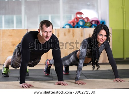 personal trainer in a gym helps do the exercise - stock photo