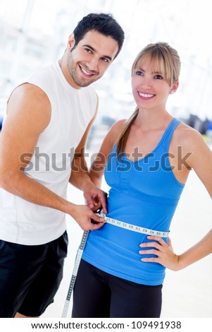 Personal trainer measuring a woman waist at the gym - stock photo