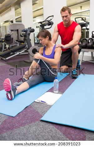 Personal trainer rubbing clients shoulders on mat at the gym