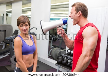 Personal trainer shouting at client through megaphone at the gym - stock photo
