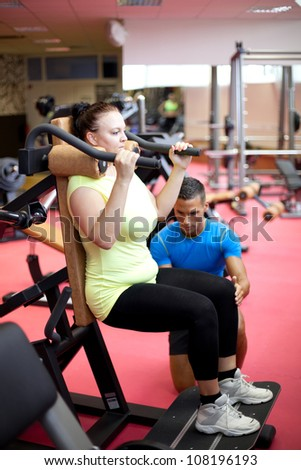Personal trainer showing a woman how to properly execute a leg exercise