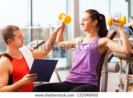 Personal trainer showing an exercise to a woman - stock photo