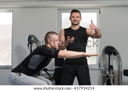 Personal Trainer Showing Ok Sign To Client - Young Man Exercising On Bosu Balance Ball In Machine A The Gym - stock photo