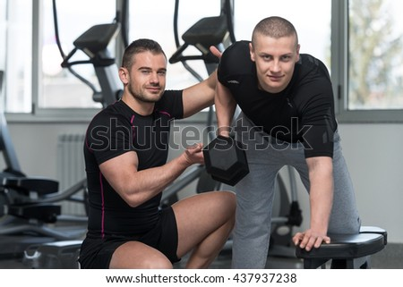 Personal Trainer Showing Young Man How To Train Back Exercise With Dumbbell In A Health And Fitness Concept