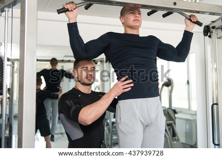 Personal Trainer Showing Young Man How To Train Pull Ups - Chin-Ups In The Gym - stock photo