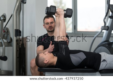 Personal Trainer Showing Young Man How To Train Triceps Exercise With Dumbbell In A Health And Fitness Concept - stock photo