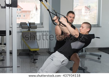 Personal Trainer Showing Young Man How To Train With Trx Fitness Straps In A Health And Fitness Concept - stock photo