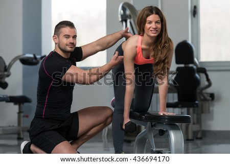 Personal Trainer Showing Young Woman How To Train Back Exercise With Dumbbell In A Gym
