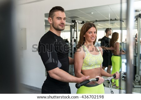 Personal Trainer Showing Young Woman How To Train Biceps On Machine In The Gym - stock photo