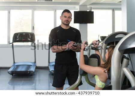 Personal Trainer Showing Young Woman How To Train Chest On Machine In The Gym - stock photo