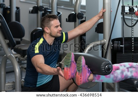 Personal Trainer Showing Young Woman How To Train Legs On Machine In The Gym - stock photo