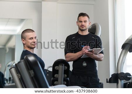 Personal Trainer Takes Notes While Young Man Exercise Legs On Machine In The Gym