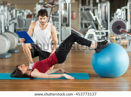 Personal trainer training a woman in the gym