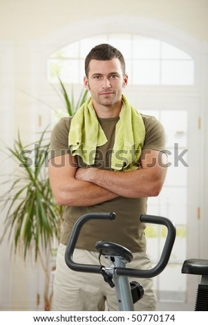 Personal trainer wearing sportswear and towel standing in living room at home with training bike, smiling. - stock photo