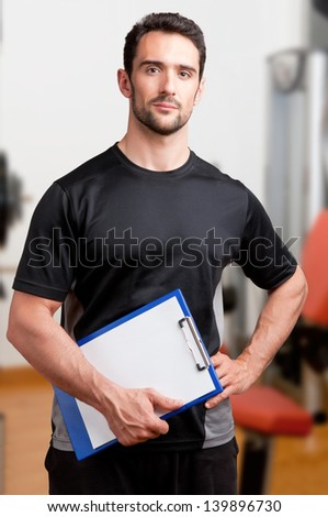 Personal Trainer, with a pad in his hand, in a gym - stock photo