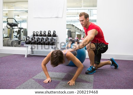 Personal trainer with client doing push up on exercise ball at the gym - stock photo