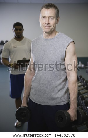 Personal trainer with middle-aged client at gym