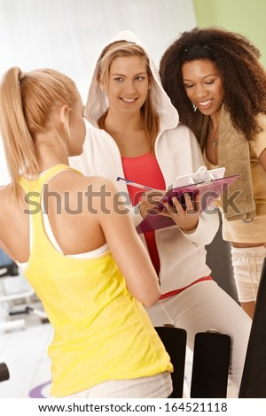Personal trainer working at the gym, smiling. - stock photo