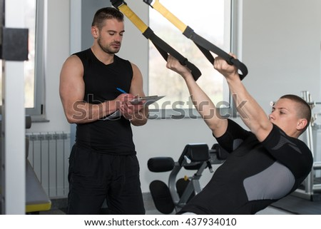 Personal Trainer Working With A Young Man At The Gym Writing Notes On A Clipboard In A Health And Fitness Concept - stock photo