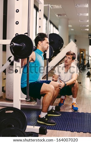 Personal trainer working with his client in gym helping him with squats - stock photo