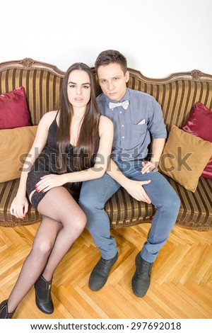 Persons in luxury interior. Attractive couple, pair of lovers at ancient living room sitting on couch or sofa. Portrait of handsome fashionable man with charming woman posing indoor. Lust and passion. - stock photo