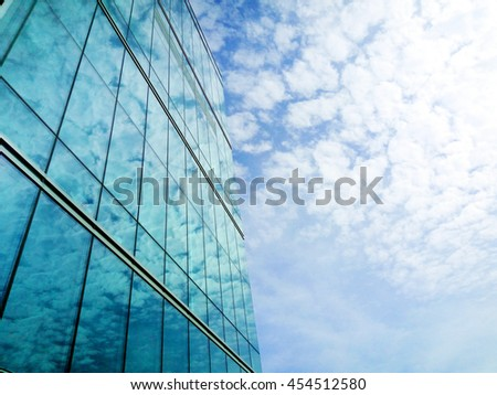 Perspective and underside angle view to textured background of beautiful modern glass building skyscrapers over blue cloudy sky