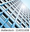 Perspective and underside angle view to textured background of contemporary glass building skyscrapers at night - stock photo