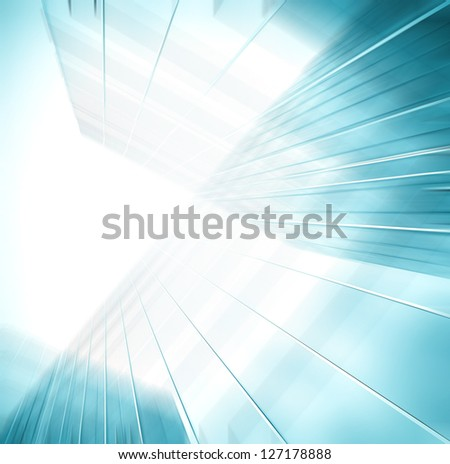 Perspective and underside angle view to textured background of contemporary glass building skyscrapers in the morning - stock photo