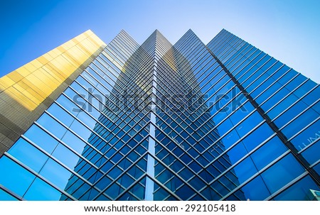 Perspective and underside angle view to textured background of modern glass  blue building skyscrapers roof - stock photo