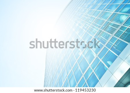 Perspective and underside angle view to textured background of modern glass building skyscrapers over blue bright clear sky with sunlight - stock photo