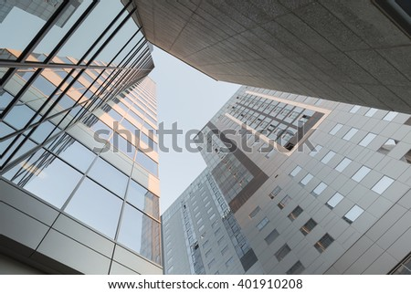 Perspective and underside angle view to textured background of modern glass office skyscraper buildings roof