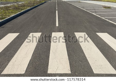 Perspective of an asphalt road with crosswalk stripes in the foreground